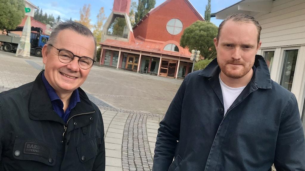 Två män i blå jackor på ett torg