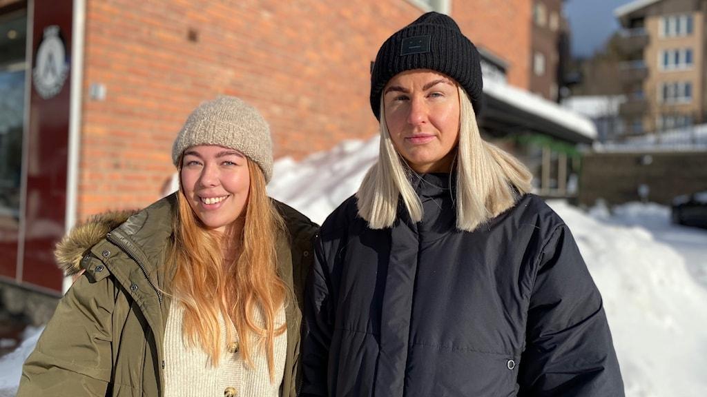 En rödhårig kvinna och en blond kvinna står utomhus framför en tegelvägg och en liten snöhög.
