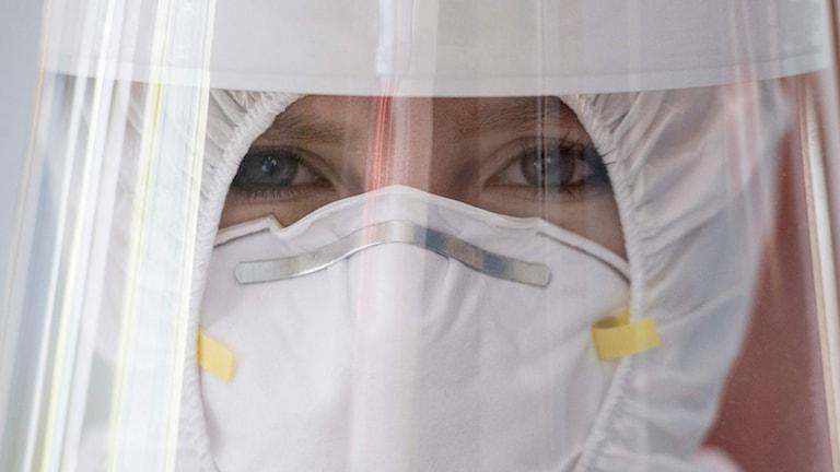 Närbild av en kvinna i vit skyddsmask, visir och skyddsdräkt där bara ögonen syns