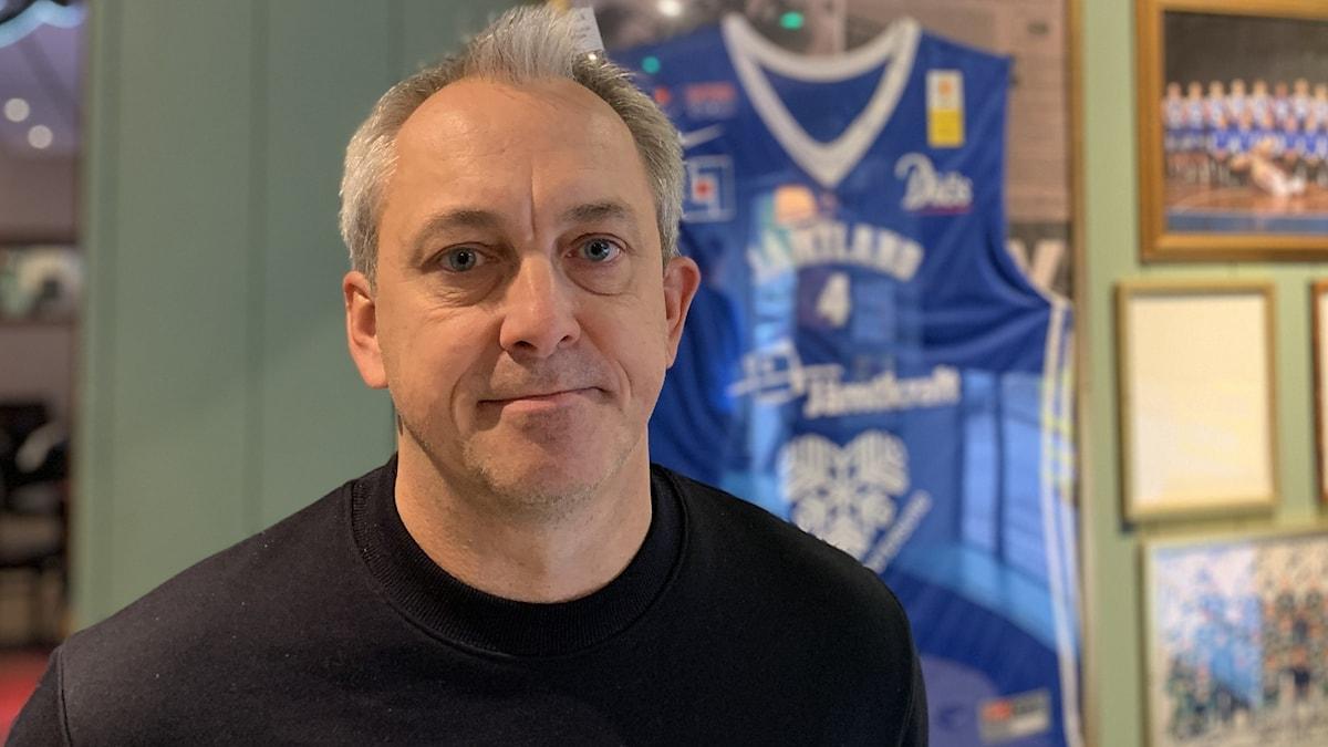 En tunnhårig man i svart tröja framför basketsouvenirer