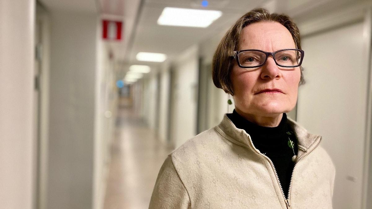 Kvinna i glasögon och mörkt kortklippt hår som står i en ljus korridor.