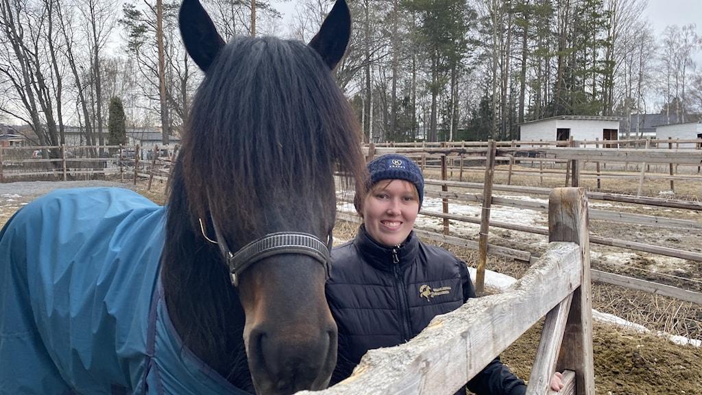 En glad, ung, tjej står innanför ett staket intill en mörkbrun häst med lång lugg.