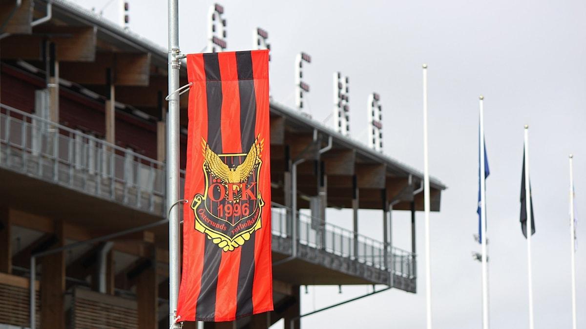 Röd-svart ÖFK-flagga på hög stolpe framför idrottsarena