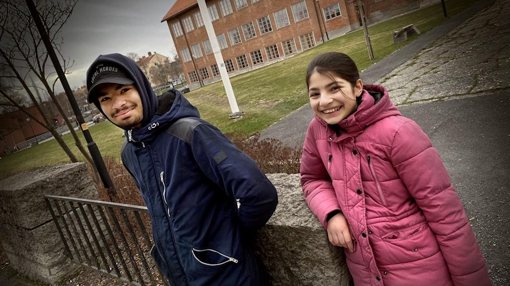 Pojke i keps och hoodie, och tjej i rosa lång täckjacka framför skolbyggnad.