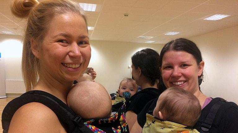 två kvinnor med varsitt barn i bärsele