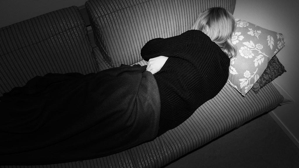 Kvinna liggande på bädd.