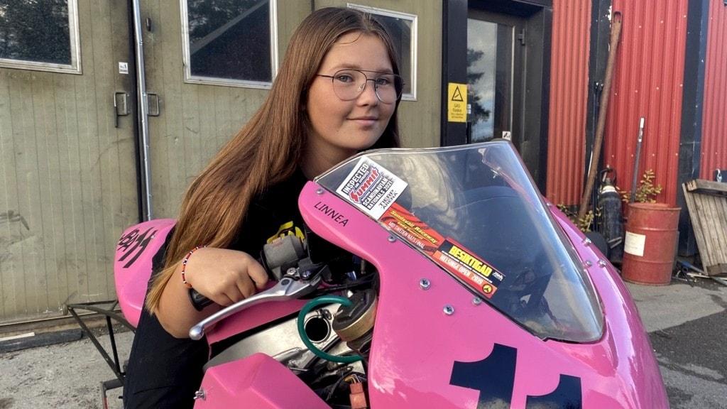 Flicka 15 år sitter på rosa motorcykel