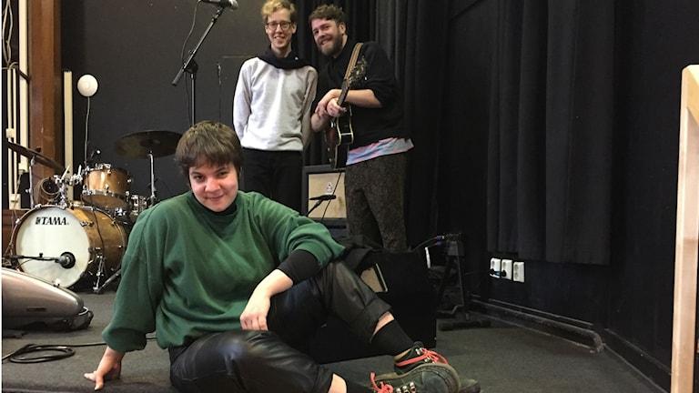 Tre musiker står på scenen och ler in i kameran, i bakgrunden ett trumset