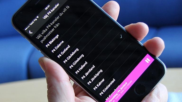 Hand håller mobiltelefon med inställning för Sveriges Radios pushnotiser