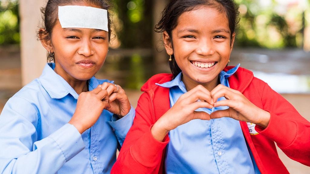 Två barn som formar hjärtan med sina händer.