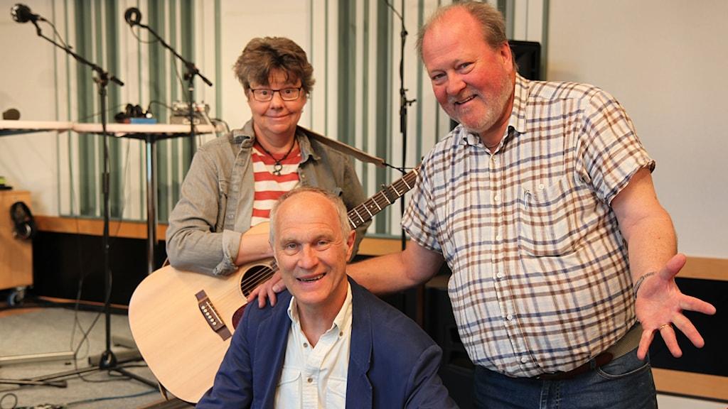 Två män och en kvinna med gitarr i en radiostudio