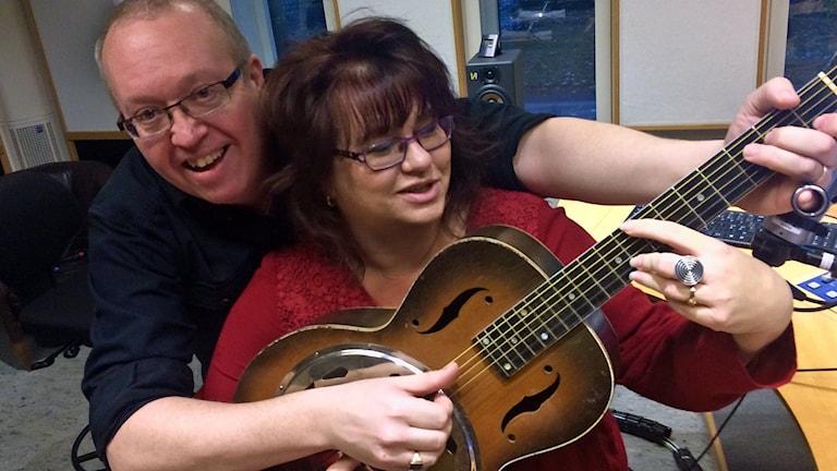 man och kvinna spelar på en gitarr
