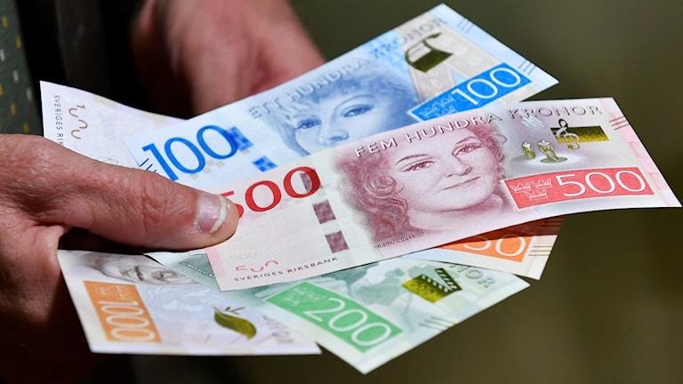 Hand håller sedlar