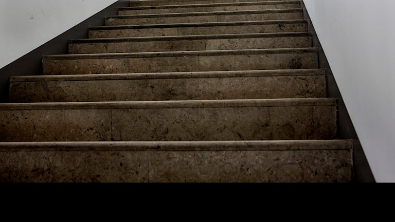 En brant stentrappa i en trapphall.
