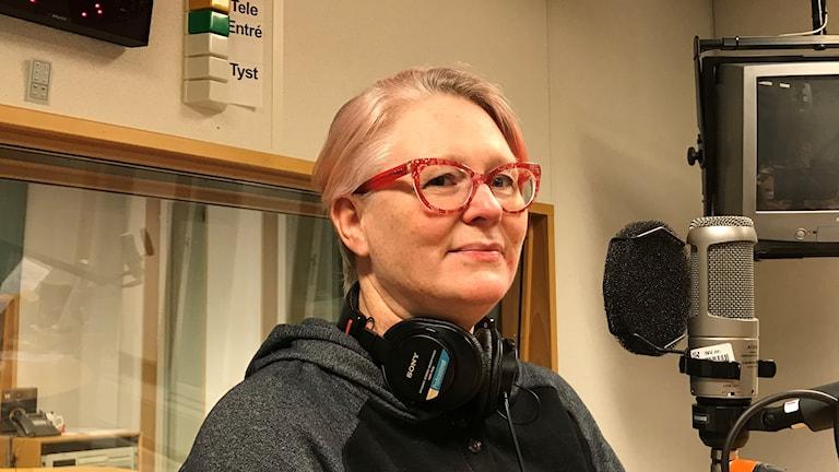 Kvinna med hörlurar framför mikrofon i radiostudio