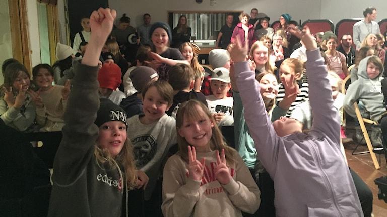 Barn ler och gör segertecknet i en radiostudio