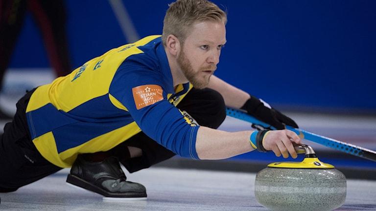 Curlingspelaren Niklas Edin i färd med att spela en sten