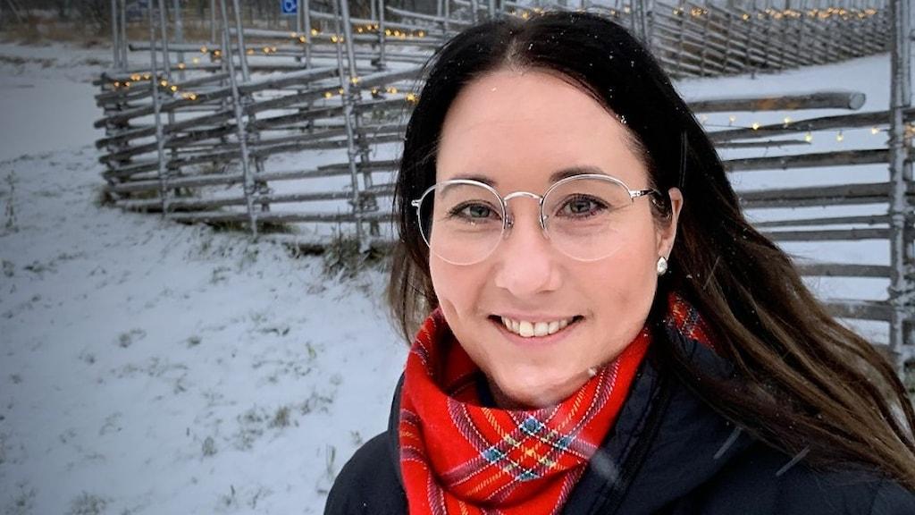 Långhårig kvinna framför snötäckt gärdesgård.