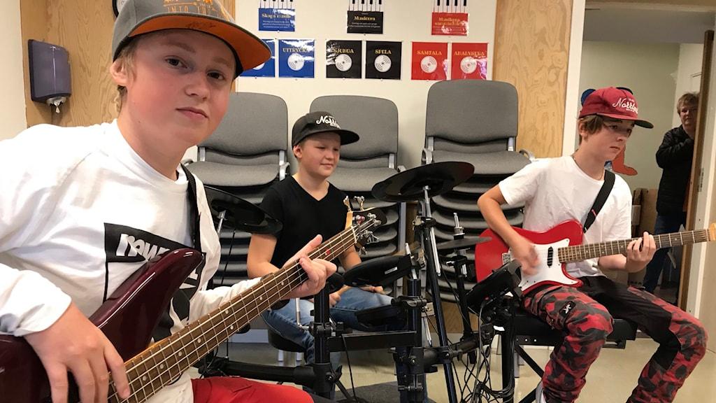 Tre killar som sitter vid varsitt instrument, en bas, en gitarr och ett trummset.