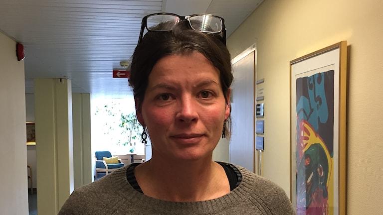Kvinna står i korridor med glasögon i håret.