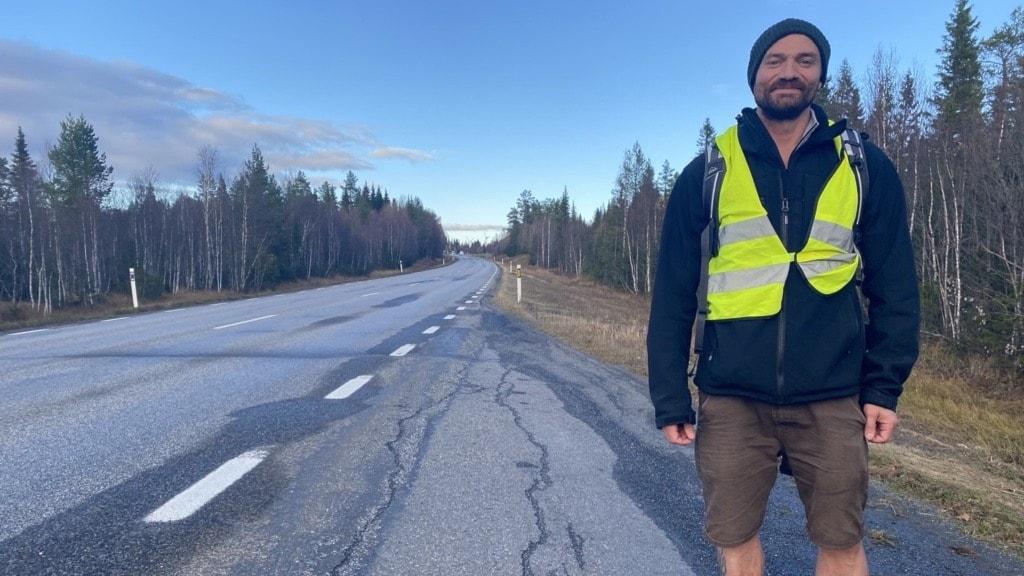 Man som är barfota längs en asfalterad väg