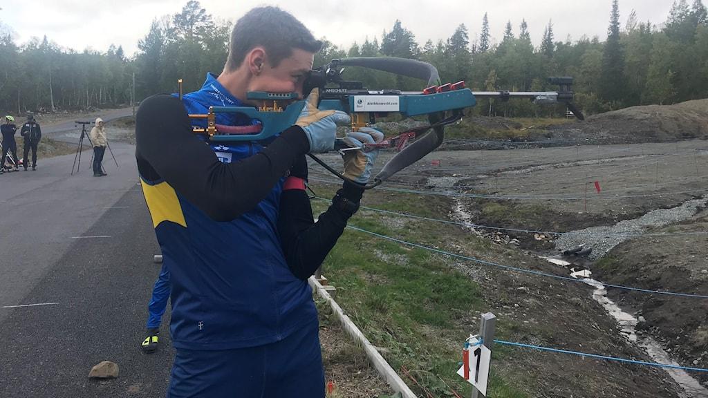 En ung man som tränar skidskytte står på skjutbanan med höjt gevär.