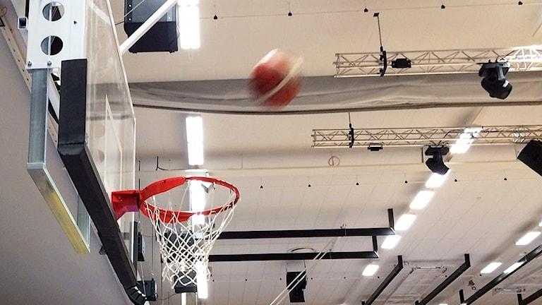 Basketboll i luften på väg mot basketkorgen