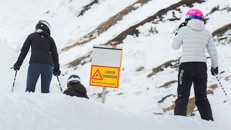 Utförsåkare åker förbi en skylt som varnar för lavinområde