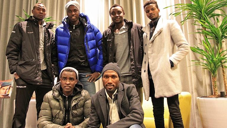 Sex män uppställda för lagbild i foajé