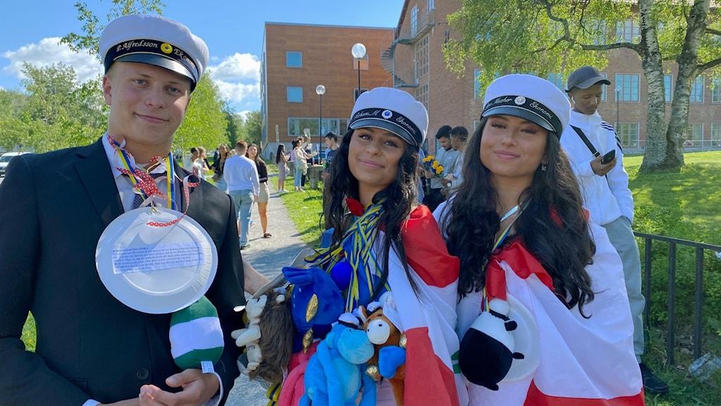 Två studentklädda tjejer och en kille i solsken med flaggor