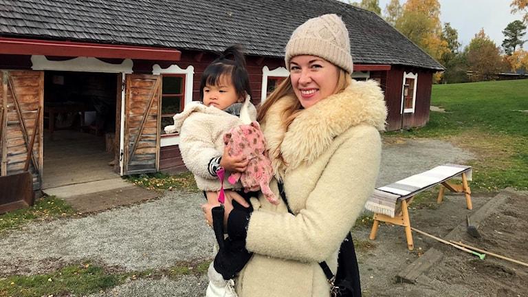 En mamma håller sin lilla dotter i famnen utanför en gammal röd lada på Jamtli i Östersund.