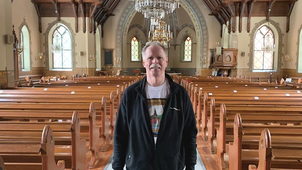 Man står inne i en kyrka, mitt i gången fram till altaret. I kyrkan finns träbänkar, stora fönster och en ljuskrona som hänger från taket.