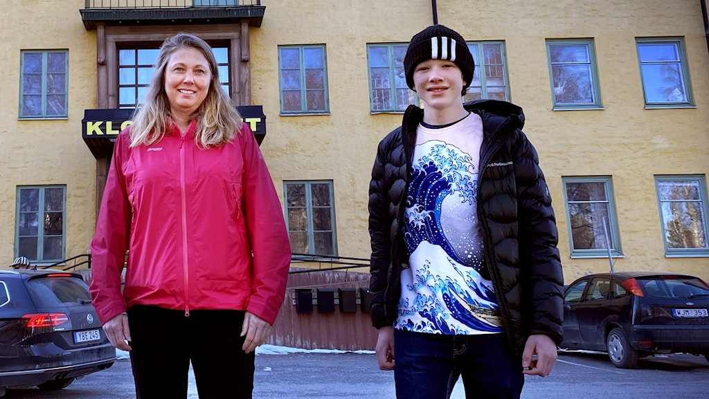 Två elever på varsin sida om av en kvinnlig lärare framför stor gul byggnad.