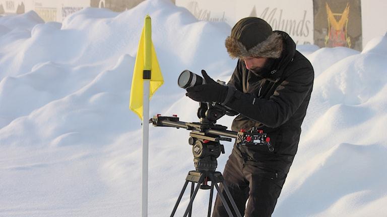 Vinterklädd man filmar på snötäckt fotbollsarena