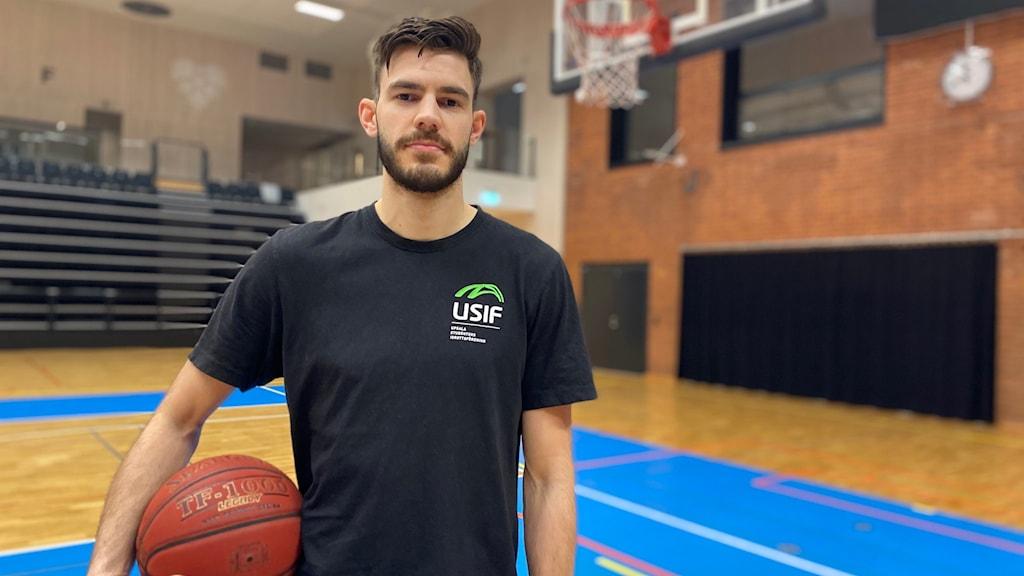 En basketspelare står med en basketboll under armen och blickar in i kameran.