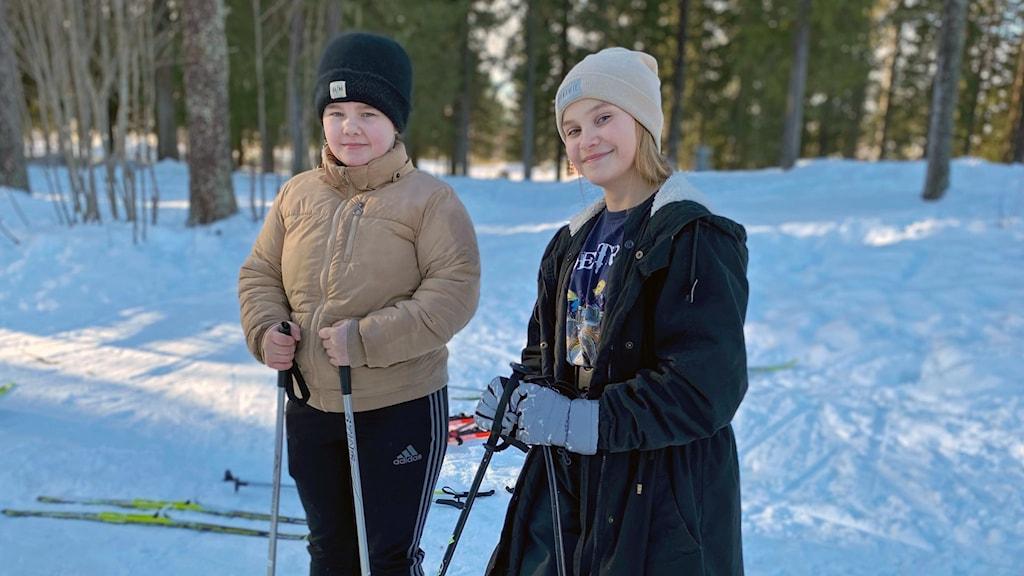 Två flickor som står på längskidor i skogen