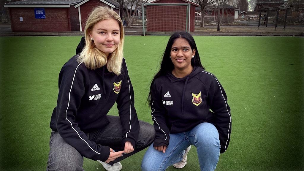 Två fotbollsklädda tjejer med fotbollsplan som bakgrund.
