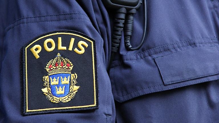 Närbild polismans skjortärm med emblem samt kommunikationsradio