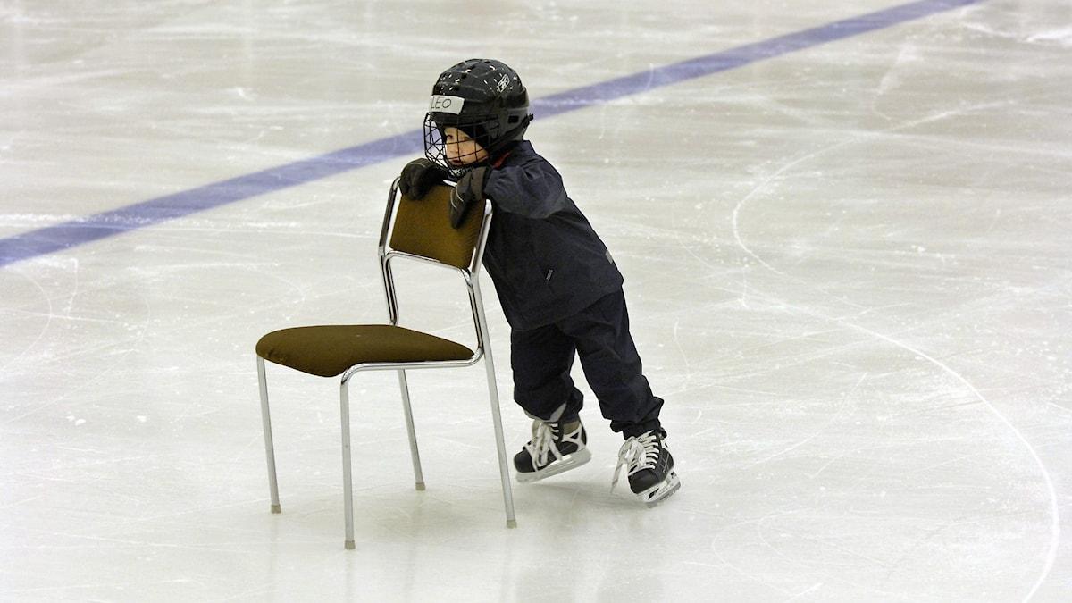 ett barn som åker skridskor med hjälp av en stol som stöd
