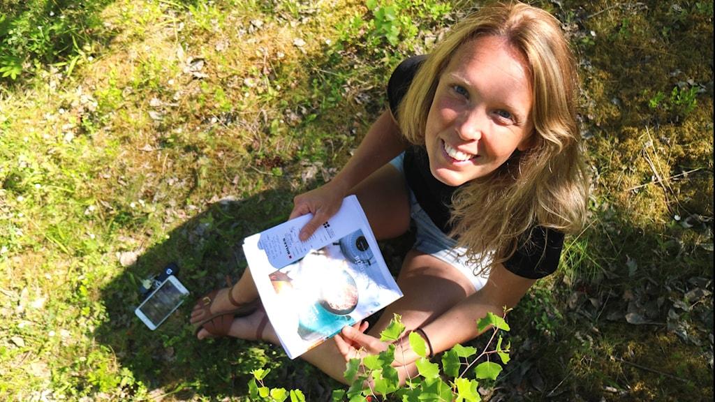 Ung kvinna med långt, blont hår sitter på gräsmatta med receptblad i händerna