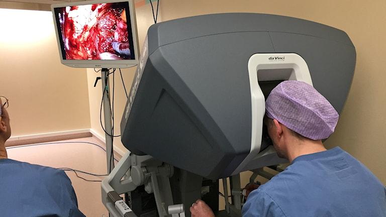 Läkare styr terminal till operationsrobot och operation visas på bildskärm i operationssal