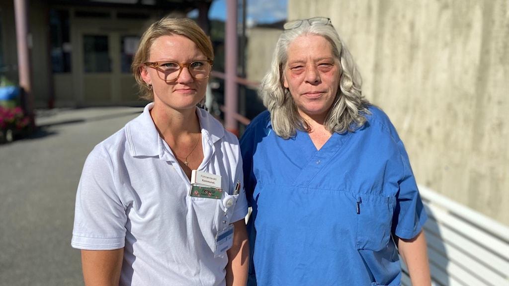 Två blonda kvinnor står utanför en teglebyggnad i solskenet.