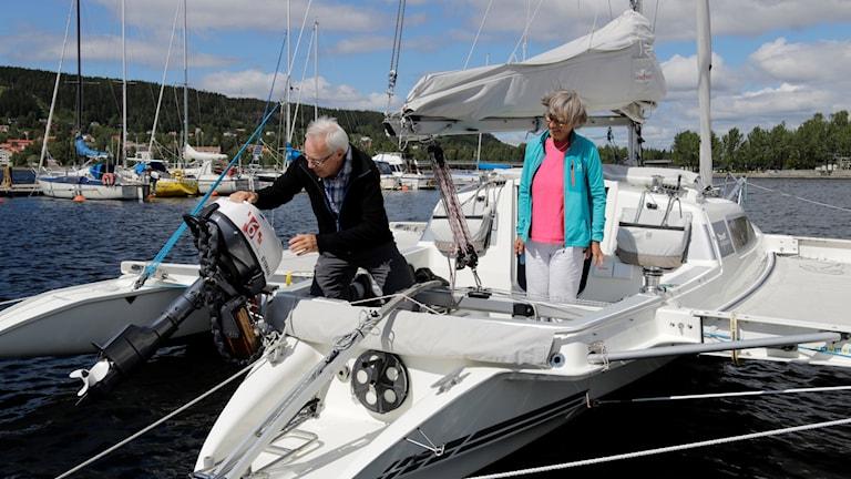 Två äldre människor, en man och en kvinna, på en vit segel-trimaran, storsjön och några båtar i bakgrunden