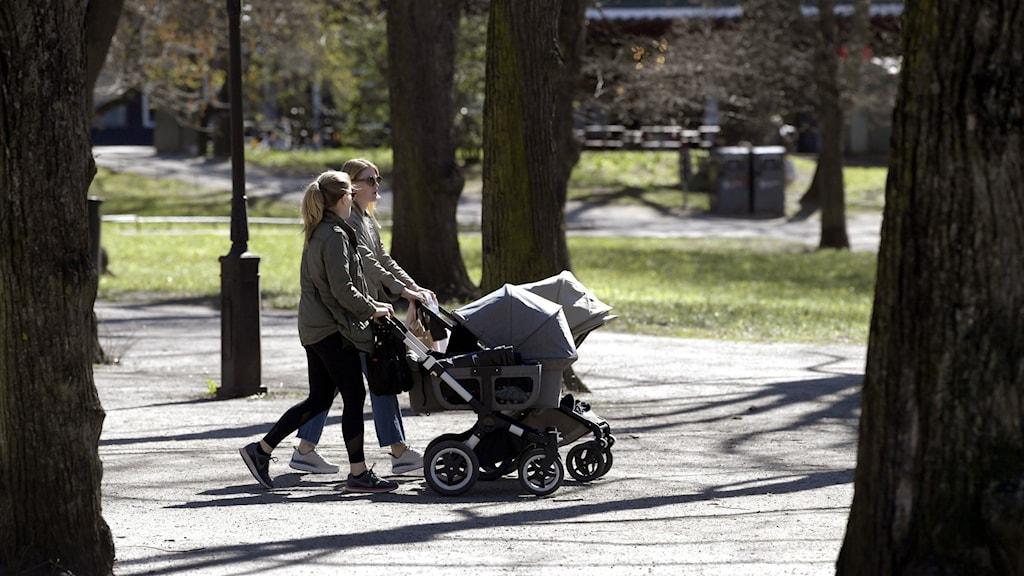 Två yngre kvinnor med barnvagn.