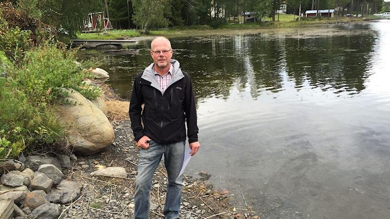 Lasse Göransson står på stranden i Mjälaviken.