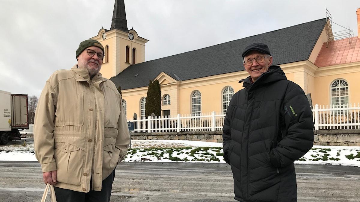 Två män som står framför en beige kyrka.