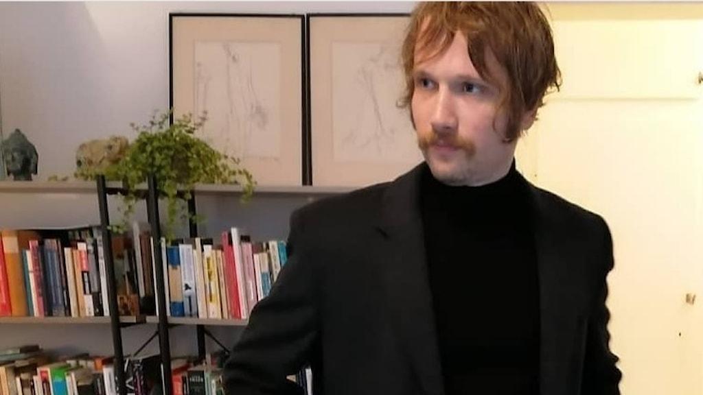 Svartklädd med mustasch.