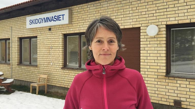 Kvinna står framför byggnad med en skidgymnasium skylt i bakgrunden.