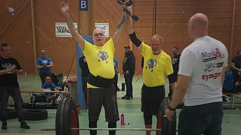 En man sträcker upp sina händer i luften som en segergest