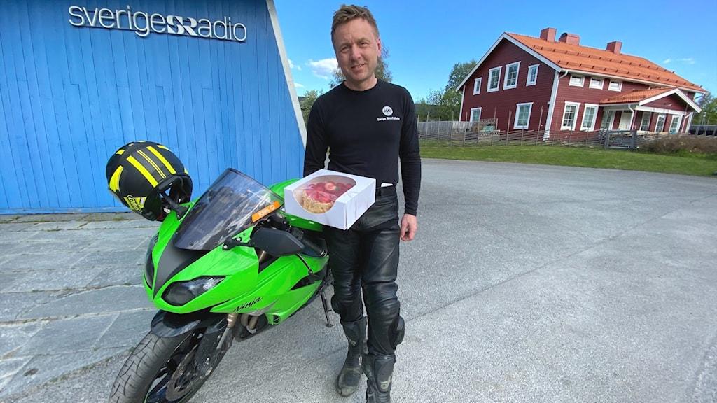 Man i svarta kläder står bredvid motorcykel och håller fram en jordgubbstårta